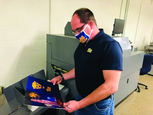 Scott Ruta admires the UV coating on a piece he ran through the Duplo DDC-810 raised spot UV coater at University of Pittsburgh Printing Services.