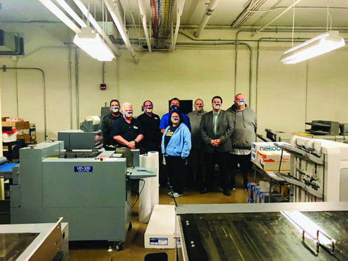 The University of Pittsburgh Printing Services team poses behind the shop's Duplo UD-300 diecutter. From left: John Ruggieri, John Schnupp, Scott Ruta, Joe Barca, Theresa White, David Doerfler, Robert Fitzgerald, and Paul Mahowski.