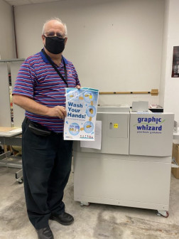 Steve Priesman displays a sample of what the Omaha Public Schools in-plant can laminate with the help of its Graphic Whizard PT33LSC.