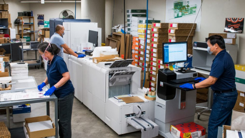 Inside Documents and Media, Lisa Gee (left) works on social distancing posters, while Edmond Brillantes and Richard Lee (right) run the Xerox Iridesse.