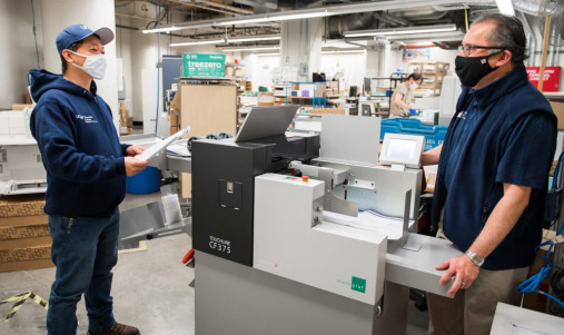 Emiliano Mamaradlo, Jr. (left) and Mario Carmona discuss the patient education materials being creased and folded on the Duplo CF375.