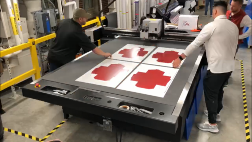 Nicholas Payne discusses a job being cut on the Esko Kongsberg X24 contour cutter with customers Jonathan King and Ryan Adams from Alabama Football.