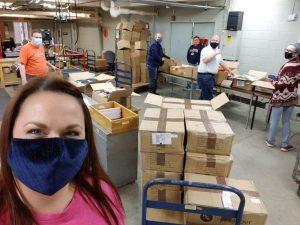 Liz Bowden (left) and members of her crew from different parts of the printing and mailing operation at the University of Illinois, Urbana-Champaign work together to stuff boxes of items that will ship to students. From left: Robert Murphy, Julie Knapp, Jeff Purcell, Devin Dariotis-Pridgen, and Sarah Walters.