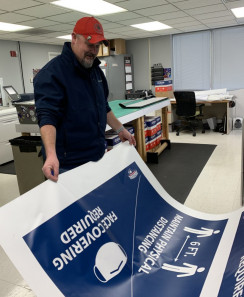 Bill Forston checks a social distancing graphic being printed at the University of Southern Indiana's in-plant.