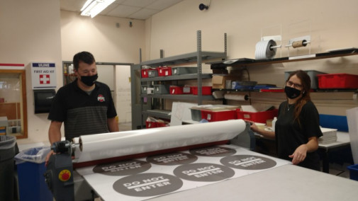 Brian Campbell and Paige Watts laminating COVID signage.