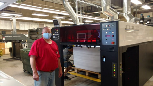 Press Operator Jim Jones stands with the new five-color Komori Lithrone G37 press.