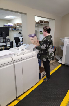 Erin Fizer reviews a proof of COVID-19 safety signage being printed at The University of the South.