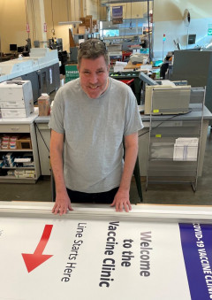 At University of Washington Creative Communications, Scot Winn works on signage for the COVID-19 vaccine clinic.