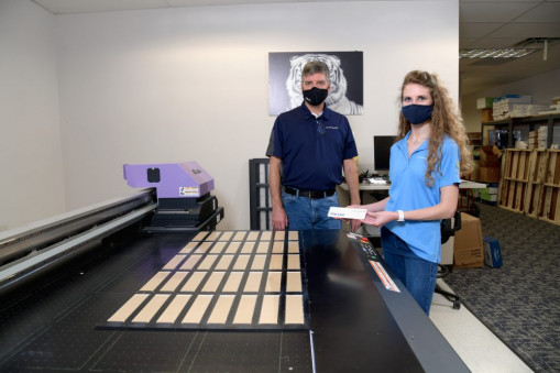 Kirk Blomquist and Cristin Morgan stand with the Dallas operation's Mimaki flatbed printer, set up with a jig that allows 40 acrylic name plates to be printed at once.