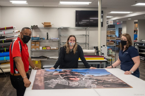 Showing off a wide-format project in the Orlando operation are Darnell Harris, Erica Linn, and Stacy Blair.