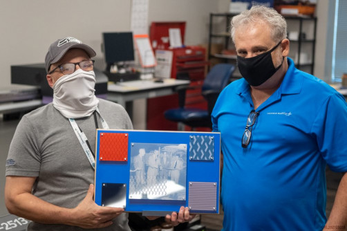 Tom Ferry and Mark Di Saverio hold up a sample graphic used to decorate a cafeteria wall in the Orlando facility.