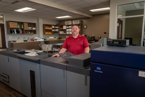 Troy Ahonen, print production supervisor for the Minnkota Power Cooperative, stands with his in-plant's Konica Minolta AccurioPress C6100.