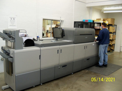 An AIC runs one of the shop's Ricoh digital printers, which are mostly used to print internal Department of Corrections work.