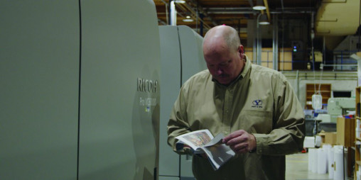 Digital Print Production Manager Ben Bean pages through a book printed on the in-plant's Ricoh Pro VC60000 inkjet press, which it installed in 2019.