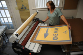 Heather Bloom uses the new Phoenix 440-ML mounting laminator to laminate directional signage for Juniata College.