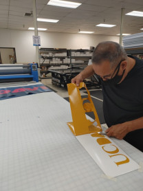 Cut vinyl is a frequently used sign-making technique for the team at UC Davis Repro Graphics. Here, Johnny Flores prepares a vehicle sign composed of cut lettering from the Mimaki UCJV 300-160.