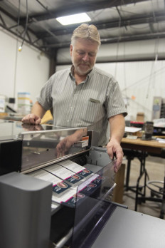 Lewis Lubeck, senior bindery technician, monitors the quality of a project being slit on the Duplo DC-746 slitter/cutter/creaser.
