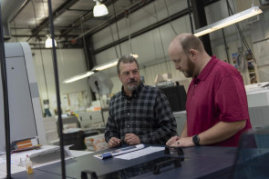 Don Guldan (left), prepress technician, and DuWane Sessions, digital print technician team lead, review a proof before production begins on the Canon varioPRINT i300 production inkjet press.