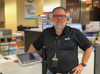David Campos stands with one of the in-plant's Riso Valezus T2100 inkjet printers.