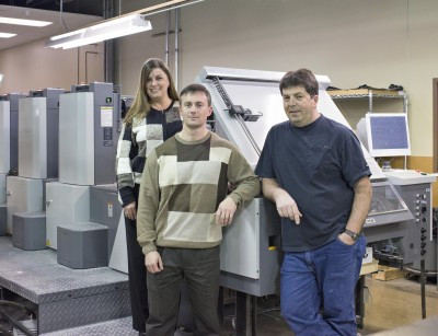 Showing off Penn State's new four-color Ryobi 764E press are Customer Service Coordinators Stacy Ostrofsky and Chris Keeler along with Joe Krisch, press operator.