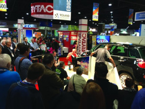 A crowd gathers to watch Roland techs wrap a car.