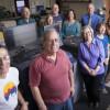 Production Printing team members stand around the in-plant's new Konica Minolta C1100 bizhub PRESS.
