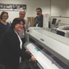 At Omaha Public Schools, Lead Artist Shelly Dutiel (foreground) runs a banner on the Mutoh VJ1638 printer, while Plant Specialist Janet Hula, Manager Steve Priesman and IT Technician Jeff Wild look on.