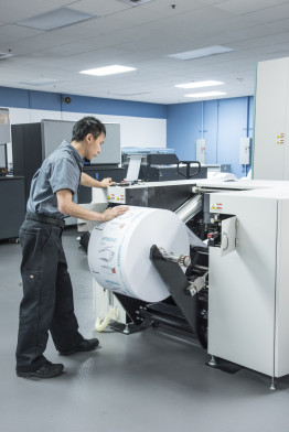Operator Max Hsu unloads a printed roll  from the Fujifilm J Press 540W.
