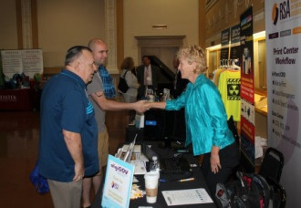 Attendees visit the vendor area during one of the breaks. Fifteen companies displayed their products and services this year.