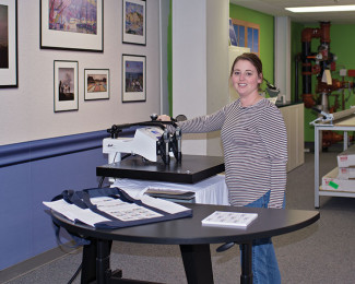 Prepress Operator Mandee Eckert demonstrates the dye-sublimation process by using a heat press to fuse an image onto a shirt.