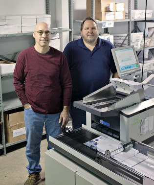 Adding a new Neopost DS-200 folder/inserter in 2016 enabled the in-plant to take on fulfillment of student acceptance packets and reduce turnaround time significantly. Standing with the inserter are Keith Fornwalt, operator, and Bob Eichman, premail coordinator.