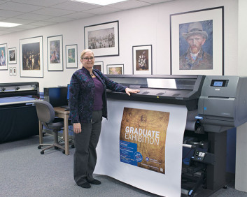 Manager Theresa Roby shows off a print produced on the in-plant's HP Latex 330. The wall behind her has been wrapped with a graphic depicting a collection of framed artwork.