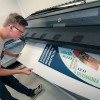 Eagle Images student assistant Wilson Haynes inspects a poster being printed on the HP 360 latex printer.