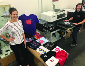 Laura Swan (left) displays samples of shirts printed on the in-plant's Brother GT-381 direct-to-garment printer, being operated by Laura Garber (right).
