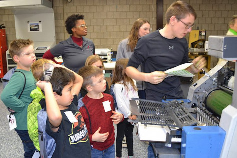 CVCC student teaching local elementary students about offset printing.