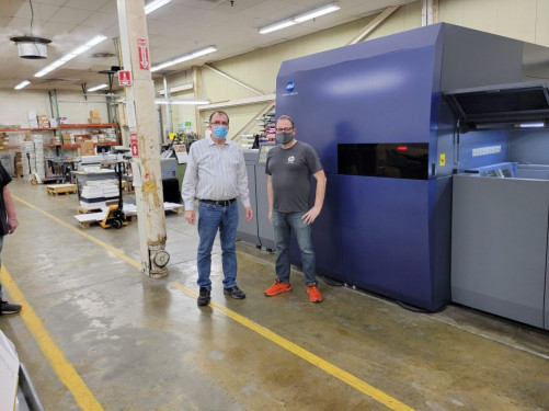 Standing with the Konica Minolta AccurioJet KM-1 sheetfed inkjet press at GHP Media are John Vesia (left), VP of manufacturing, and Kyle Moran, lead operator.