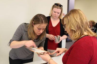 Andrea McConnaughey and Tammy Dunham confer over an entry, while Erica Derrington looks on.