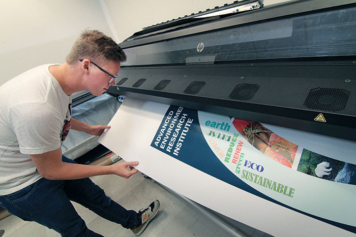 Eagle Images Student Assistant Wilson Haynes Inspects A Poster Being Printed On The HP 360 Latex