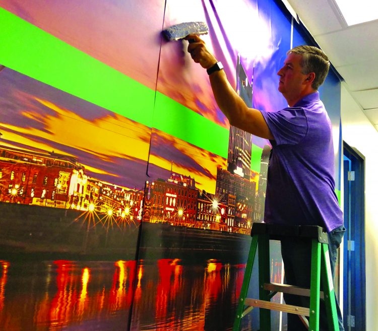 Kris Tanner of Schneider Electric mounts a wall graphic.